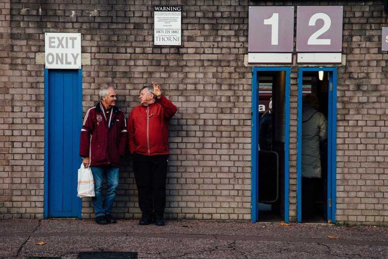 2 men standing outside Burnley football club