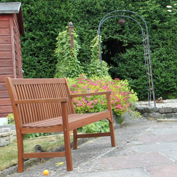 Wooden garden chari with hedge in background