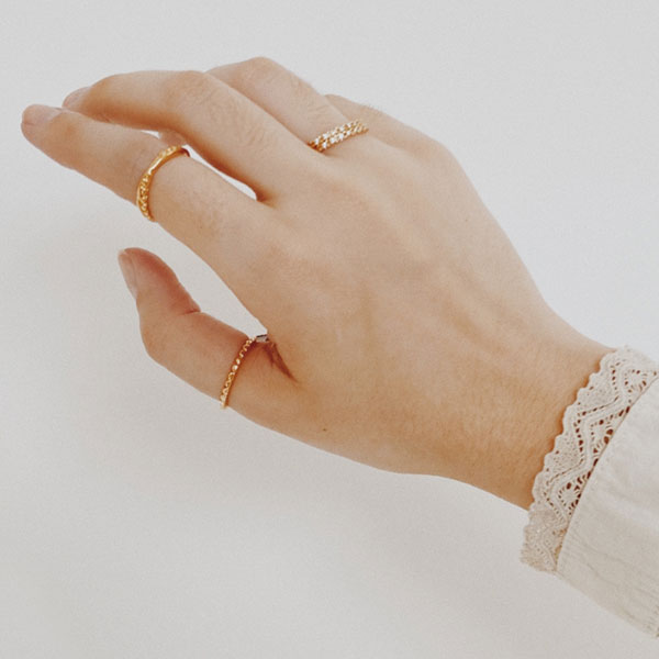 A hand wearing rings