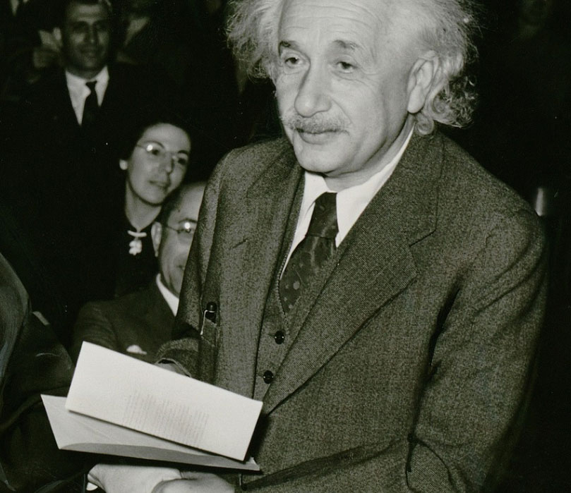 Albert Einstein holding an envelope. An audience can be seen in the background.