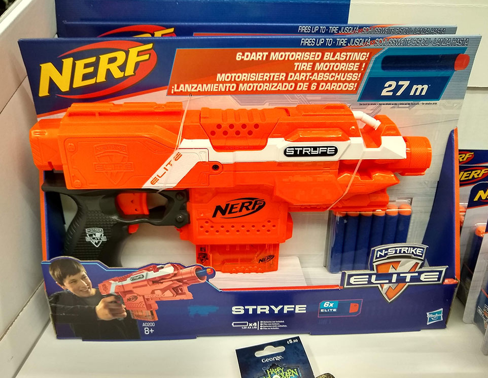 A Nerf Gun Stryfe in packaging on a shop shelf. There is a picture of a boy holding a Nerf Gun on the packaging.