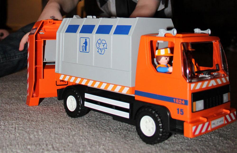 A plastic Playmobil bin lorry in grey and orange.