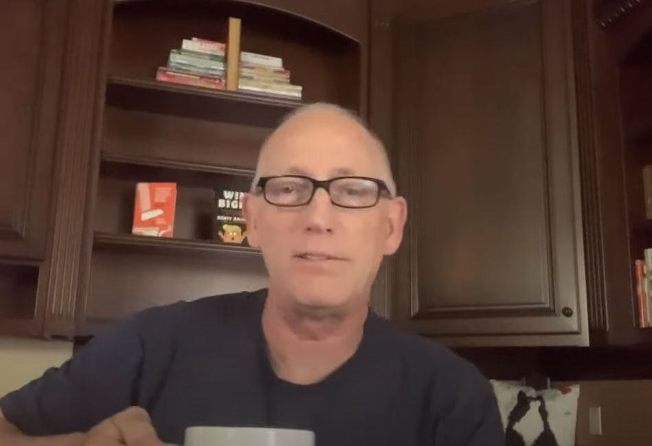 Scott Adams holding a coffee cup and sitting in his kitchen. Behind him are his book Win Bigly and How To Fail At Almost Anything