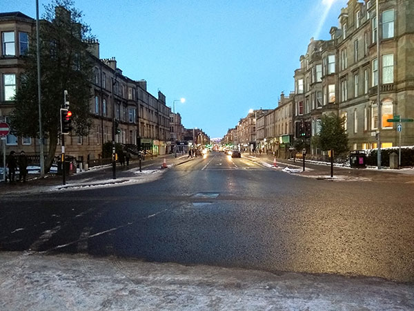 A road in Glasgow lined by tenements on either side.